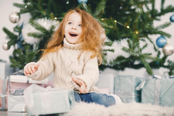 beautiful blonde girl opening gifts 600x400